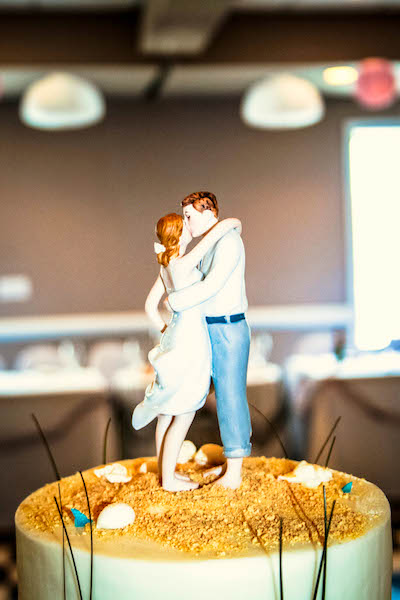 Have your cake and eat it too at the Sea Ranch Resort Wedding Venue, This couple enjoys a moment on top of a wedding cake at the sea ranch resort in kill devil hills, We have an oceanfront wedding venue for you outer banks beach wedding at the sea ranch resort